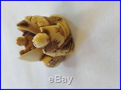 Netsuke. Fine carving of a men holding a baby in a shell. Signed